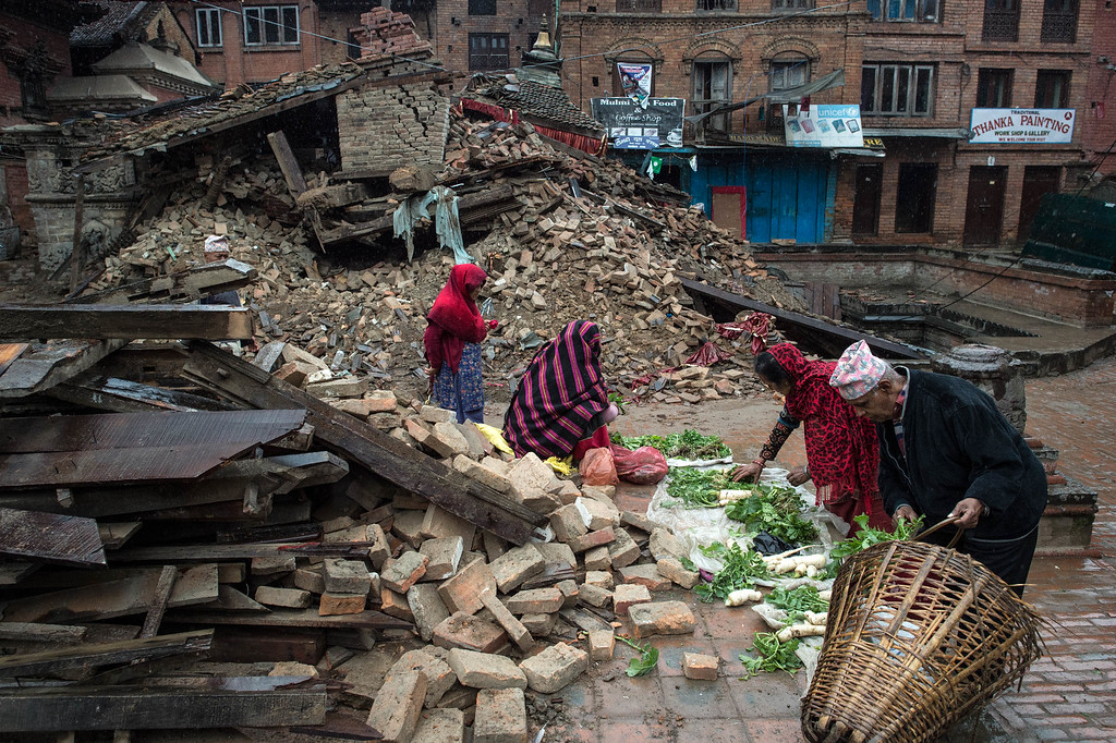 . Nepalese victims of the earthquake buy vegetables on the street next to debris of a collapsed temple in Bhaktapur on April 30, 2015 in Kathmandu, Nepal. A major 7.8 earthquake hit Kathmandu mid-day on Saturday, and was followed by multiple aftershocks that triggered avalanches on Mt. Everest that buried mountain climbers in their base camps. Many houses, buildings and temples in the capital were destroyed during the earthquake, leaving over 5500 dead and many more trapped under the debris as emergency rescue workers attempt to clear debris and find survivors. Regular aftershocks have hampered recovery missions as locals, officials and aid workers attempt to recover bodies from the rubble.  (Photo by David Ramos/Getty Images)