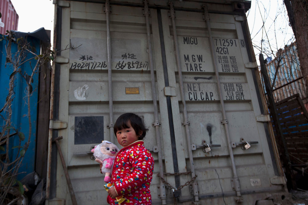 Description of . A child holds her toy as she stands outside shipping containers serving as her accommodation, in Shanghai March 4, 2013. The containers, which house different families, were set up by the landlord, who charges a rent of 500 yuan ($ 80) per month for each container. REUTERS/Aly Song