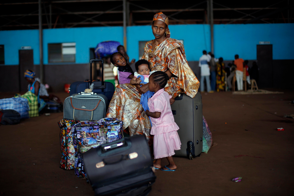 . A Chadian family waits for transport to Chad in a hangar at Bangui\'s airport in Bangui, Central African Republic, Thursday Jan. 30, 2014. Over 350 Muslim refugees were evacuated by the UN\'s International Organization for Migration (IOM) fleeing sectarian violence between Muslim Seleka forces and Christian anti Balaka militias. (AP Photo/Jerome Delay)