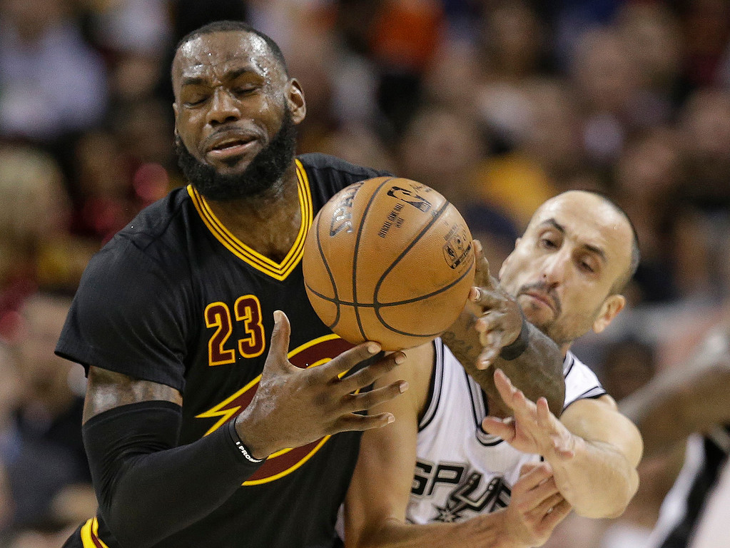 . San Antonio Spurs\' Manu Ginobili, back, from Argentina, knocks the ball loose from Cleveland Cavaliers\' LeBron James in the first half of an NBA basketball game, Saturday, Jan. 21, 2017, in Cleveland. (AP Photo/Tony Dejak)