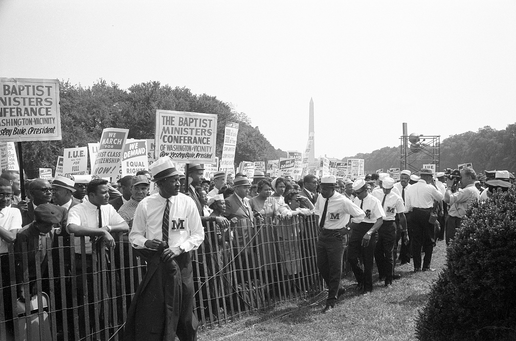 Description of . Marshalls standing by fence near crowd carrying signs, including