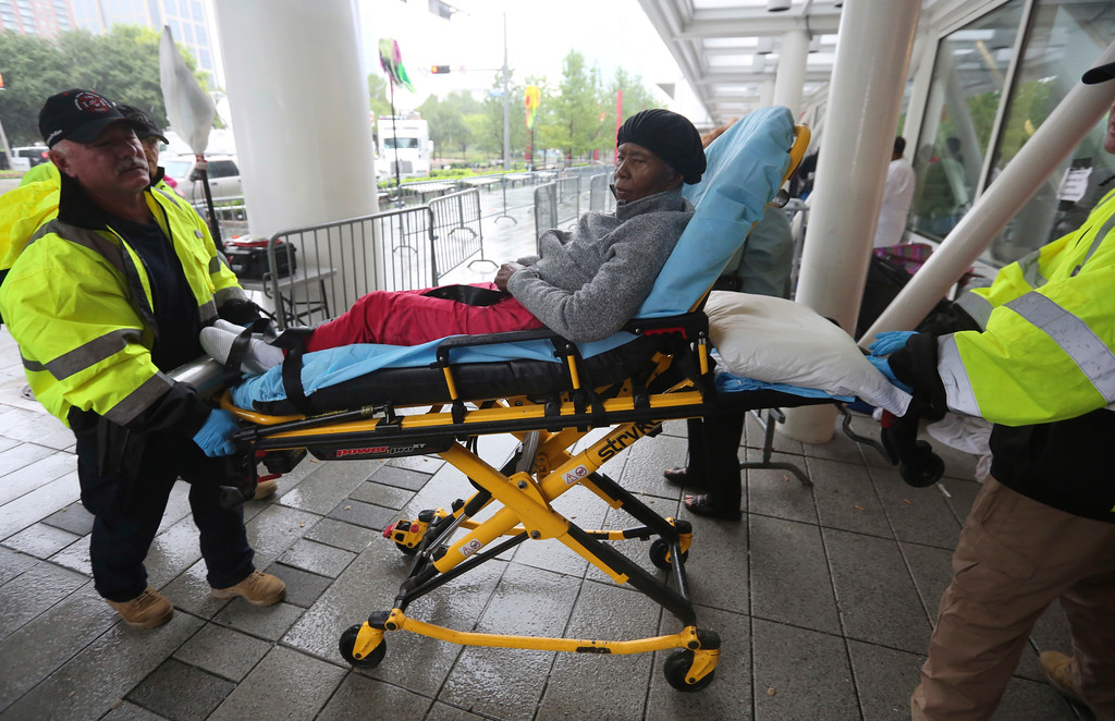 . A woman is wheeled by first responders into the George R. Brown Convention Center that has been set up as a shelter for evacuees escaping the floodwaters from Tropical Storm Harvey in Houston, Texas, Tuesday, Aug. 29, 2017. (AP Photo/LM Otero)