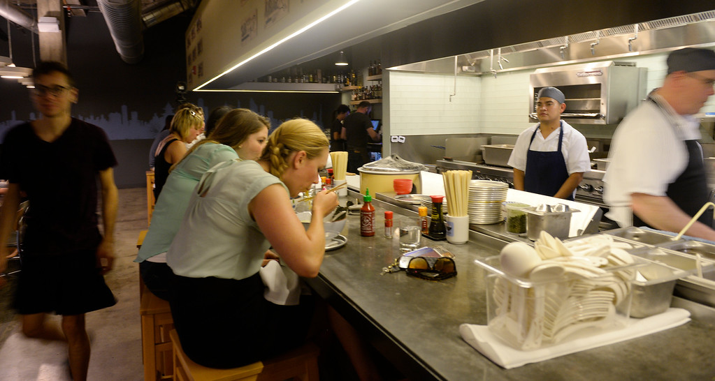 . Stephanie Mills, center, and Jennifer Anderson, right, eat ramen bowls at the counter of Osaka Ramen in Denver\'s RiNo neighborhood, 2611 Walnut St.,  on Thursday June 18, 2015.  (Photo by Cyrus McCrimmon/The Denver Post )