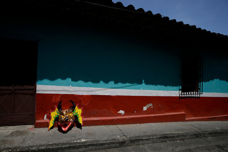 . A devil mask is propped against a wall in San Francisco de Yare, Venezuela, Thursday, May 30, 2013. The descendants of African slaves donned colorful masks and bright red costumes as they danced through the streets of this small Venezuelan town on Thursday for its annual commemoration of Corpus Christi, a Roman Catholic holiday celebrating the transformation of the body and blood of Christ into bread and wine. (AP Photo/Fernando Llano)