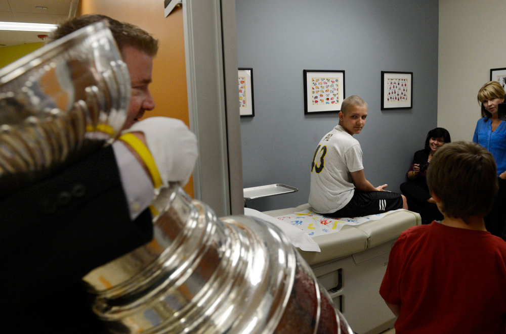 . Keeper of the Cup, Mike Bolt, surprises Logan Piz, 13, with the Stanley Cup at Rocky Mountain Hospital for Children in Denver, CO on May 15, 2013. The hospital, Make-A-Wish, Discover and the National Hockey League teamed up to grant  Logan\'s wish to spend a day with the Stanley Cup and share it with friends, family and supporters. Logan has not played hockey since he was diagnosed with Ewing�s sarcoma in November 2012. Joining Logan were his mother and father, Tammy and Ron and his brother, Hayden, 9.  (Photo By Craig F. Walker/The Denver Post)