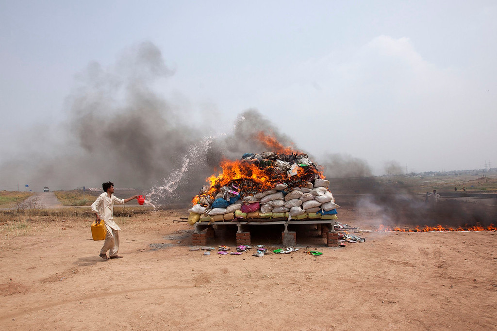 . A member of Pakistan\'s Anti-Narcotics Force (ANF) pours gasoline on a pile of confiscated drugs while setting it ablaze in observance of International Day against Drug Abuse and Illicit Trafficking, on the outskirts of Islamabad June 26, 2013. A total of 18.55 tons (37,000 lb) of drugs, including heroin, hashish, opium and morphine, were destroyed during the drug burning ceremony on the outskirts of Islamabad, the Joint Director of ANF, Colonel Mohammed Ishtiaq, said. REUTERS/Mian Khursheed
