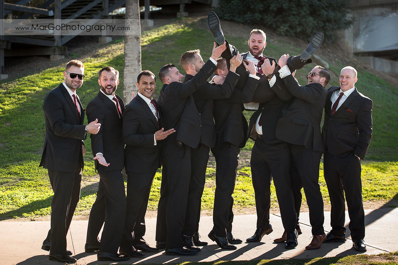 groomsmen tossing groom at San Diego Mission Bay Park
