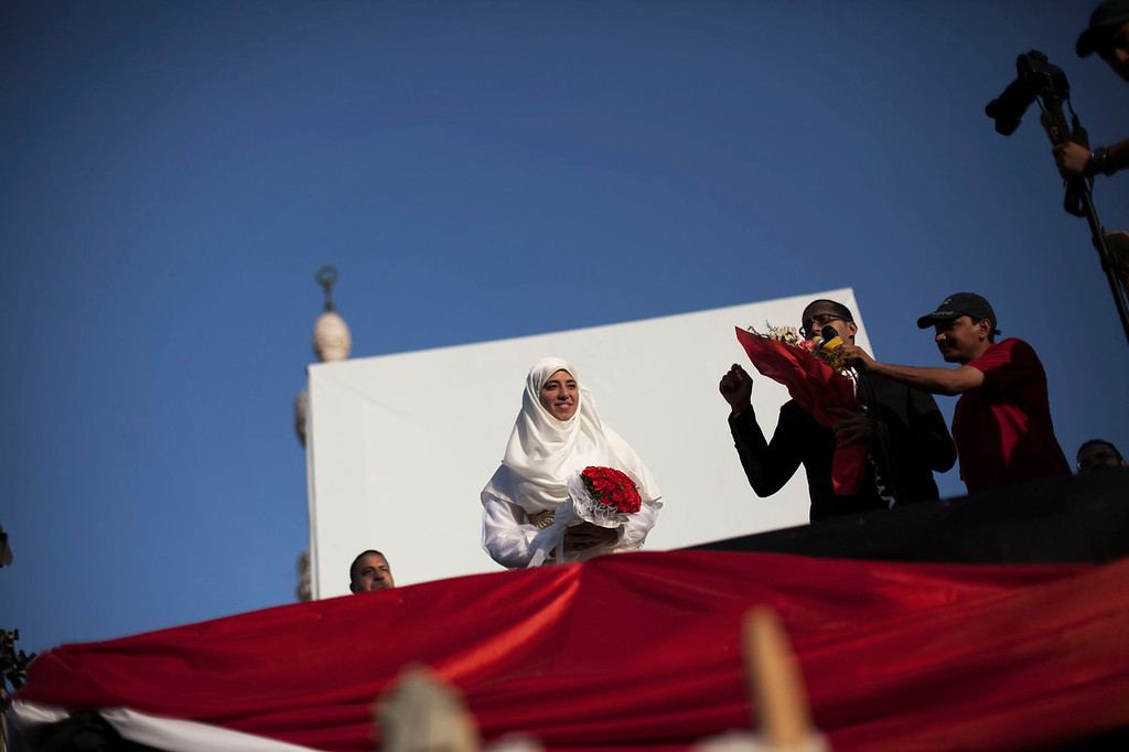 . A newly-wed Egyptian couple show up on a stage to announce their marriage before hundreds of supporters for Egypt\'s ousted President Mohammed Morsi at the sit-in at Rabaah al-Adawiya mosque, which is fortified with multiple walls of bricks, tires, metal barricades and sandbags, and where protesters have installed their camp in Nasr City, Cairo, Egypt, Sunday, Aug. 11, 2013. Egyptian security forces will besiege two sit-ins by supporters of the country\'s ousted president within 24 hours, police officials said Sunday, setting up a possible confrontation between the military-backed government and the thousands gathered there. (AP Photo/Manu Brabo)