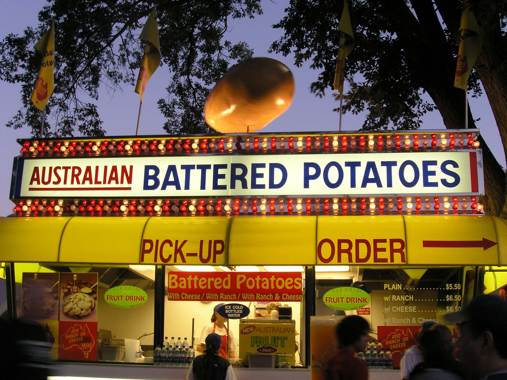 . The Australian Battered Potatoes concession stand is lit up at dusk during the 2005 Minnestoa State Fair. Photo courtesy of the Minnesota State Fair.