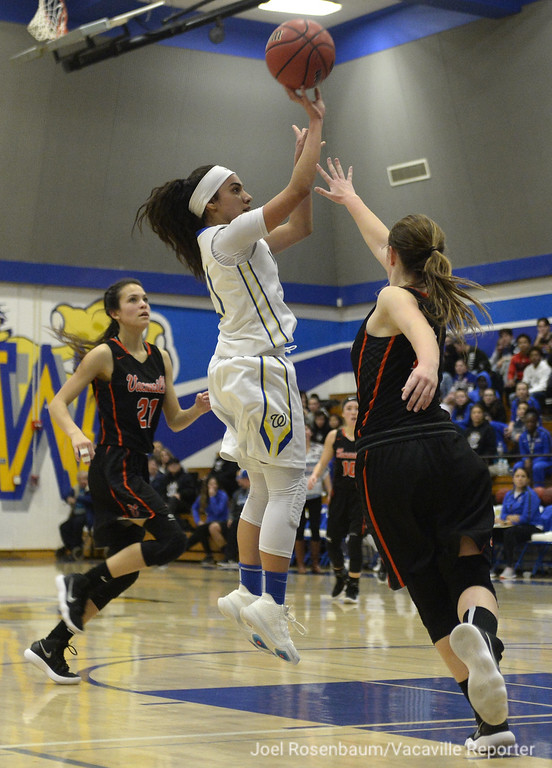 . Wood\'s Savannah Lopez fires a jump shot over the defensive pressure from Vaca High\'s Lauren Roe during the second quarter of the Wildcats victory over their rivals Thursday at Frank Molina Gymnasium. Lopez finished the game with 22 points, three rebounds and a steal.