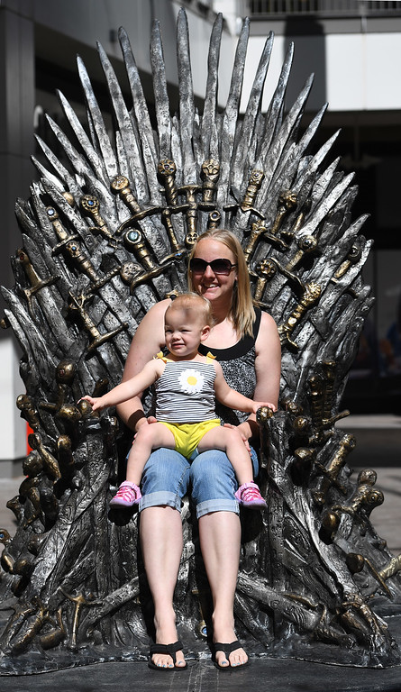 """. DENVER, CO - APRIL 22: Laura Anderson and daughter, Lucy Ward, 1, from Louisville, CO. The famous seat that characters are battling for in HBO\'s smash hit \""""Game of Thrones\"""" is now on display in the Denver Pavilions in downtown Denver for fans to pose and take pictures with for free leading up to the premiere of the show\'s sixth season on Sunday. (Photo by Kathryn Scott Osler/The Denver Post)"""