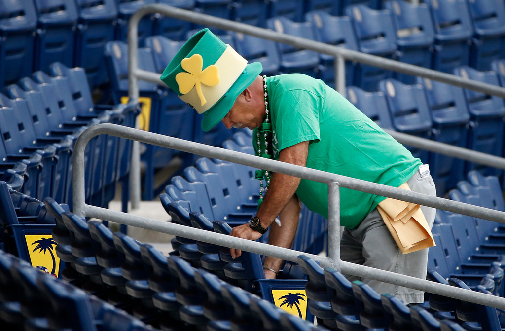 . Decked out in St. Patrick\'s Day clothing, Ed Silva of Clearwater, Fla., wipes down seats before the gates opened for a spring exhibition baseball game between the Philadelphia Phillies and the Baltimore Orioles in Clearwater, Fla., Monday, March 17, 2014.  (AP Photo/Kathy Willens)