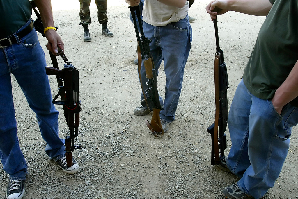 . A group of men with automatic weapons for sale stand at the gun show at the Knob Creek Machine Gun Shoot near West Point, Kentucky April 9, 2005. Thousands of machine gun and military hardware enthusiasts attended the event held each year over weekends in the spring and fall. . REUTERS/Rick Wilking