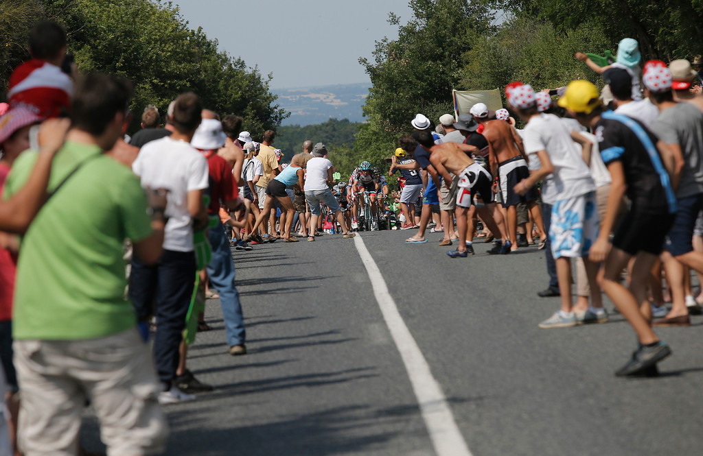 . Spectators walk up to the middle of the road to catch a glimpse of the breakaway group led by Jens Voigt of Germany during the fourteenth stage of the Tour de France cycling race over 191 kilometers (119.4 miles) with start in in Saint-Pourcain-sur-Sioule and finish in Lyon, central France, Saturday July 13 2013. (AP Photo/Laurent Cipriani)