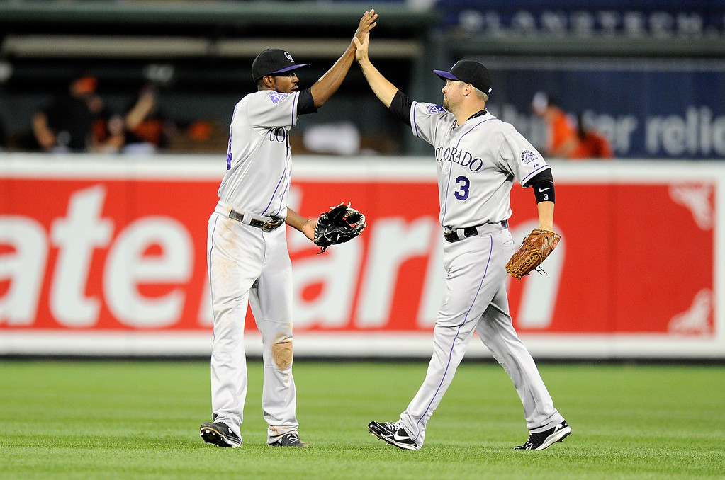 . BALTIMORE, MD - AUGUST 16:  Dexter Fowler #24 of the Colorado Rockies celebrates with Michael Cuddyer #3 after a 6-3 victory against the Baltimore Orioles at Oriole Park at Camden Yards on August 16, 2013 in Baltimore, Maryland.  (Photo by Greg Fiume/Getty Images)