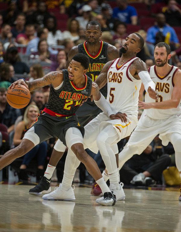 . Atlanta Hawks\' Kent Bazemore (24) controls the ball as Cleveland Cavaliers\' JR Smith (5) falls away during the half of an NBA pre-season basketball game in Cleveland, Wednesday, Oct. 4, 2017. The Hawks Dewayne Dedmon and the Cavs Kevin Love (0) watch the play from behind. (AP Photo/Phil Long)