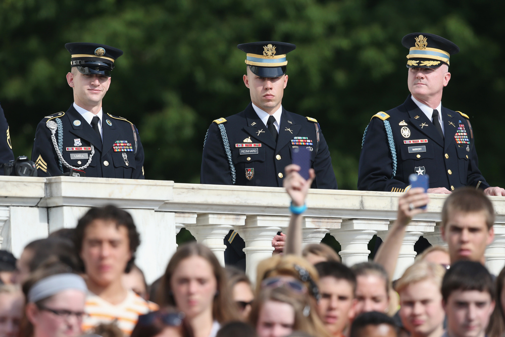 . Members of the US Army watch over people taking pictures as they wait for HRH Prince Harry to arrive during the second day of his visit to the United States at Arlington National Cemetery on May 10, 2013 in Arlington, Virginia. HRH will be undertaking engagements on behalf of charities with which the Prince is closely associated on behalf also of HM Government, with a central theme of supporting injured service personnel from the UK and US forces.  (Photo by Chris Jackson/Getty Images)