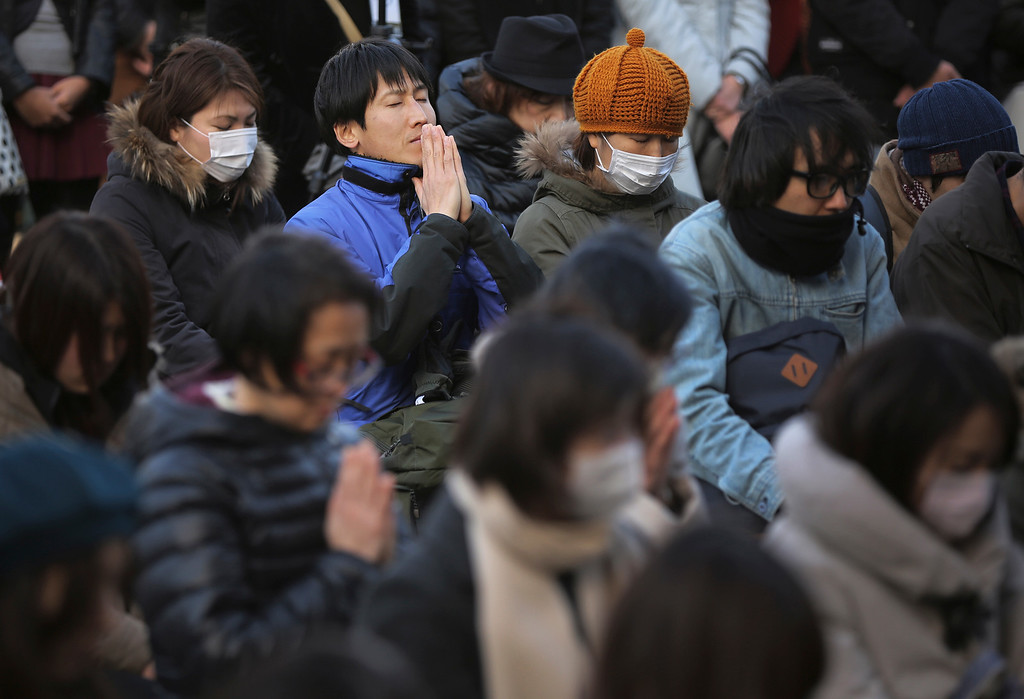 . People observe a moment of silence at 2:46 p.m. during a special memorial event in Tokyo Wednesday, March 11, 2015. Still struggling to recover, the tsunami-hit region of northeastern Japan marked the fourth anniversary of the disaster Wednesday with simultaneous moments of silence along the coast. (AP Photo/Eugene Hoshiko)