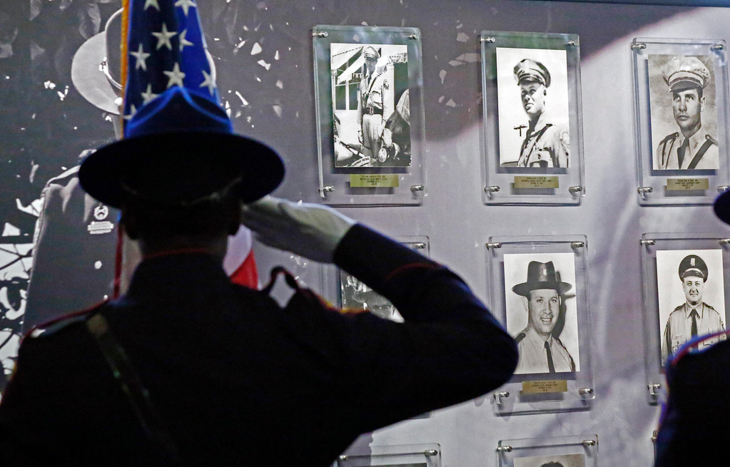 . A member of the Mississippi Highway Patrol Honor Guard salutes the memorial wall bearing the photographs of officers from the various Department of Public Safety law enforcement agencies killed in the line of duty, Tuesday, May 15, 2018, during a fallen officers memorial service at department headquarters in Jackson, Miss. (AP Photo/Rogelio V. Solis)