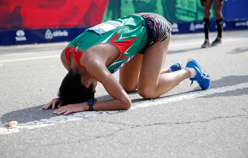 . Yuki Kawauchi, of Japan, falls to the ground after finishing in the the 44th annual New York City Marathon in New York, Sunday, Nov. 2, 2014. Kawauchi was helped from the finish line by volunteers. (AP Photo/Kathy Willens)