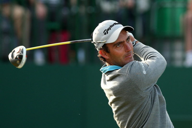 """. Italy\'s Edoardo Molinari watches his shot from the 1st tee during his first round on the opening day of the 2014 British Open Golf Championship at Royal Liverpool Golf Course in Hoylake, north west England on July 17, 2014. England\'s former Ryder Cup star David Howell got the 143rd British Open underway just after the crack of dawn at Royal Liverpool Golf Club on Thursday with all eyes early on riveted on a \""""fit again\"""" Tiger Woods. (ANDREW YATES/AFP/Getty Images)"""
