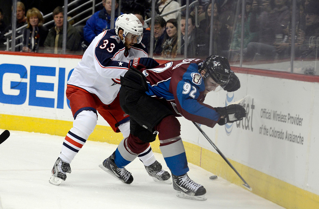 . DENVER, CO. - JANUARY 24: Columbus Blue Jackets defenseman Adrian Aucoin (33) battles with Colorado Avalanche left wing Gabriel Landeskog (92) along the boards for the puck during the first period at Pepsi Center. The Colorado Avalanche take on the Columbus Blue Jackets in NHL action.  