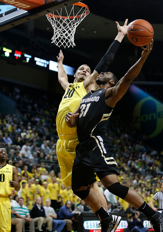 . Oregon\'s Waverly Austin (20) swats away a shot by Colorado\'s Jeremy Adams (31) during the first half of an NCAA college basketball game at Matthew Knight Arena in Eugene, Ore. Thursday, February 7, 2013. (AP Photo/Brian Davies)