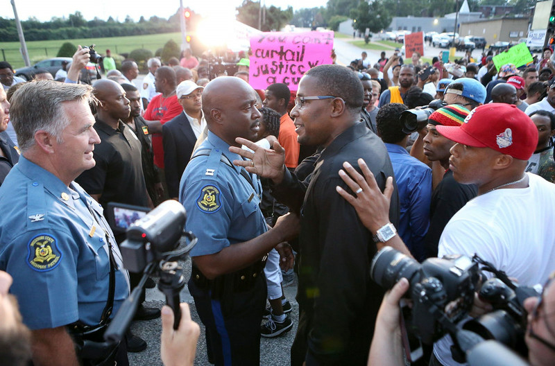 . Col. Ron Replogle, left, and Capt. Ron Johnson talk with Malik Shabazz, president of the Black Lawyers for Justice, (center) during a march with protesters along W. Florissant Avenue in Ferguson Missouri on Saturday, Aug. 16, 2014. (AP Photo/St. Louis Post-Dispatch, David Carson)
