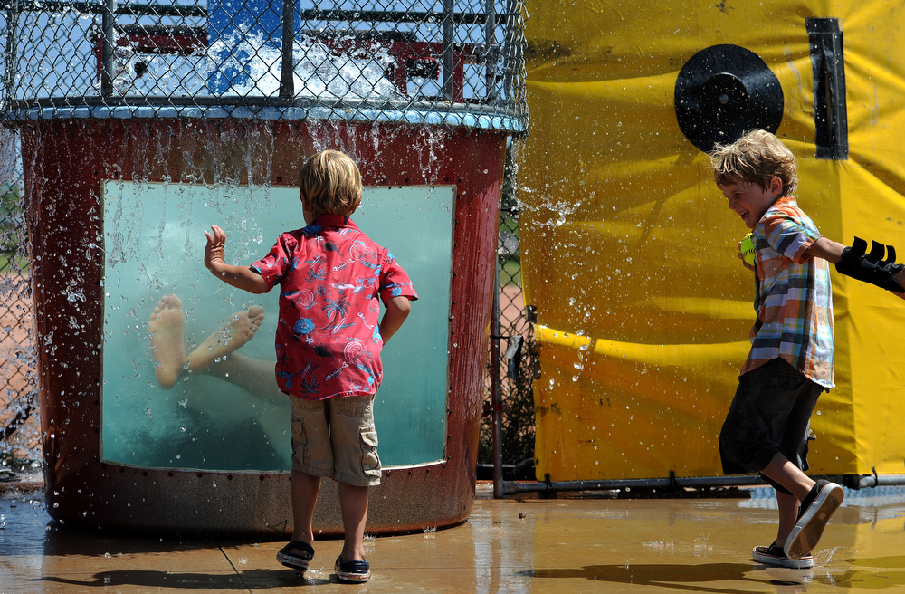 . Miles Southard, 4,  left and his brother Leo, 6, scream with laughter as they get doused in water as they watch Lt. Col Craig Wolf get dunked in the dunking pool at Buckley Air Force base in Aurora, CO on August 4, 2013.  The event was part of the 140th Wing Family Day for members of the Colorado National Guard.  Much of the money raised during the day goes to the Colorado National Guard Family Support System that helps take care of families when their loved ones have been deployed.  The Salvation Army was on hand to show their continued support for the armed services.  Photo by Helen H. Richardson/The Denver Post)