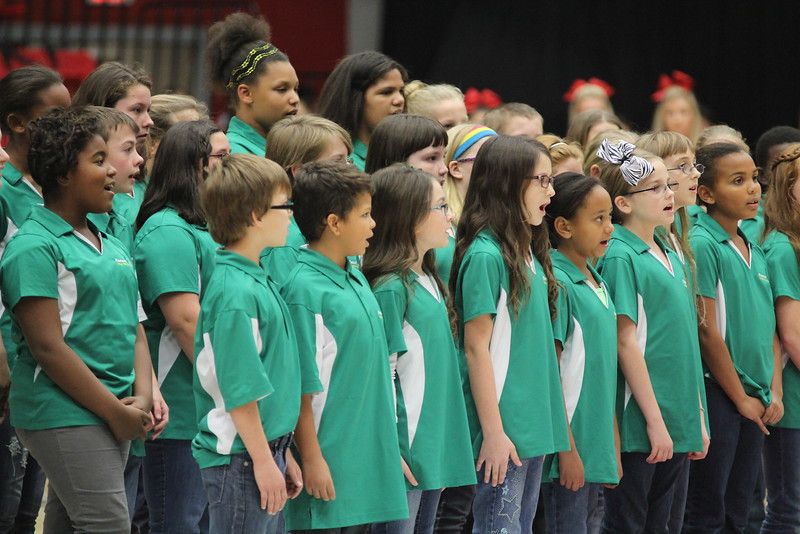 Children's choir performs the national anthem before the basketball game.