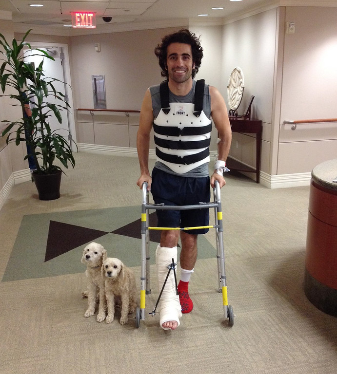 . In this Oct. 10, 2013, file photo, provided by Team Chip Ganassi Racing, IndyCar driver Dario Franchitti, of Scotland, poses with his dogs, Shug and Buttermilk, in a photo taken by his brother, Marino Franchitti, at Memorial Hermann-Texas Medical Center in Houston.  The three-time Indianapolis 500 winner said Thursday, Nov. 14, 2013, that doctors have told him he can no longer race because of injuries sustained in an IndyCar crash last month. He fractured his spine, broke his right ankle and suffered a concussion in the Oct. 6 crash at Houston. (AP Photo/Marino Franchitti, File)