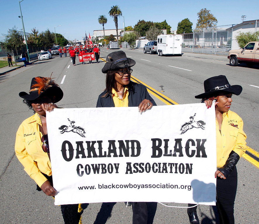 . Oakland Black Cowboy Association members Deborah Emery, Deborah Senegal and Arobia Battle, left to right, march down 18th Street near De Fremery Park during the 39th annual Oakland Black Cowboy Parade and Heritage Festival in Oakland, Calif., on Saturday, Oct. 5, 2013. The event also featured food, entertainment and pony rides for kids. The OBCA began in 1975 and educates the public about the role that black cowboys played in history and building of the west. (Jane Tyska//Bay Area News Group)