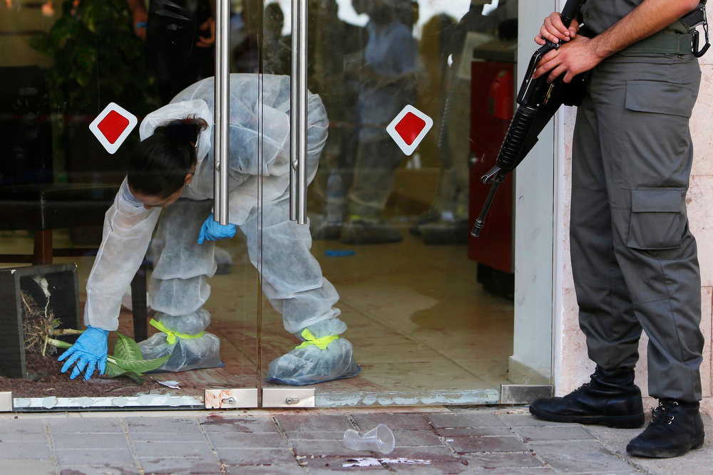 Description of . An Israeli police forensics expert is seen through the glass doors of a Bank Hapoalim branch after a shooting at the bank in the southern city of Beersheba May 20, 2013. A gunman shot dead four people execution-style in the bank in Israel on Monday after being refused an overdraft and cash from its automatic teller machine. The assailant, identified by media reports as a former paramilitary border policeman, killed himself after police raided the branch to free his hostages. REUTERS/Amir Cohen