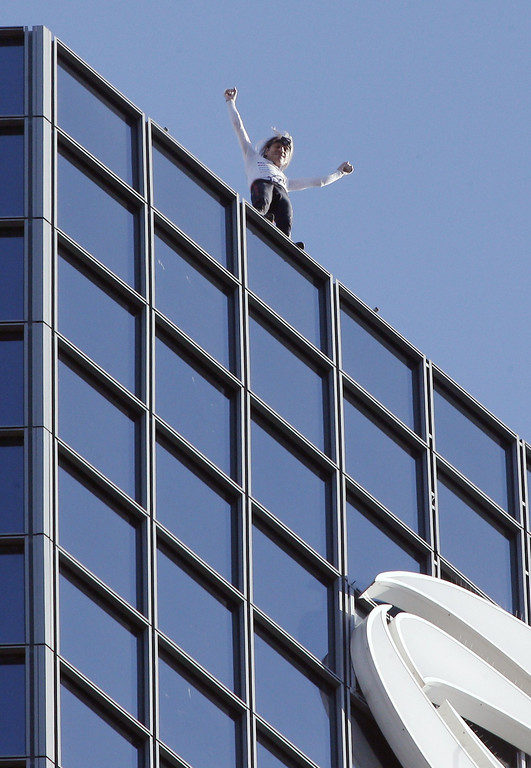 . Alain Robert, the French urban climber dubbed Spiderman, celebrates after climbing the Total company\'s headquarters, a 186-meter high skyscraper, at the business district of La Defense, near Paris, on March 20, 2014.  AFP PHOTO / FRANCOIS GUILLOT/AFP/Getty Images