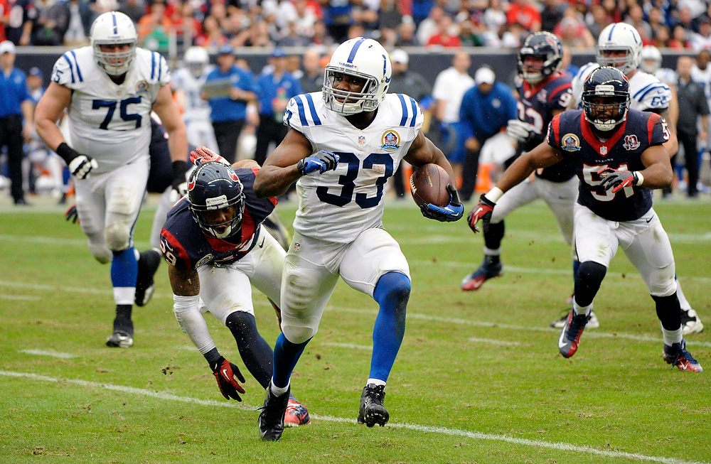 . Indianapolis Colts running back Vick Ballard (33) rushes for a gain as Houston Texans\' Glover Quin (29) and Darryl Sharpton (51) pursue in the third quarter of an NFL football game on Sunday, Dec. 16, 2012, in Houston. (AP Photo/Dave Einsel)