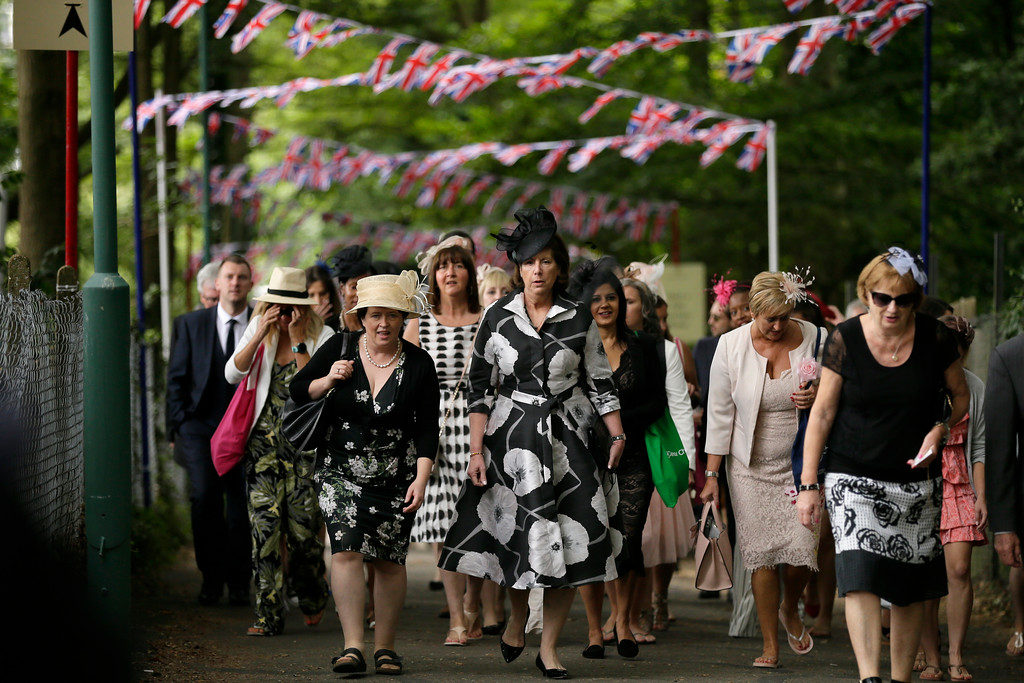 . Event visitors walk as they arrive at the Royal Ascot horse race meeting in Ascot, England, Wednesday, June 20, 2018. (AP Photo/Tim Ireland)