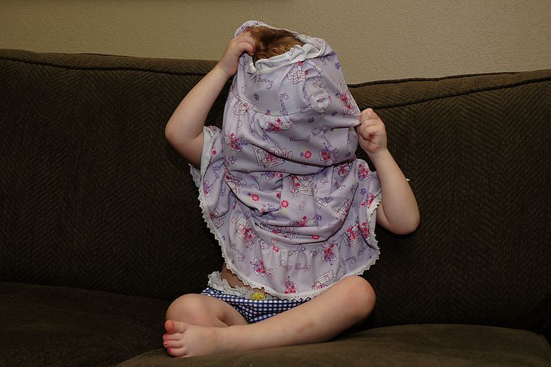 Mary hides from the camera while putting on her night gown.