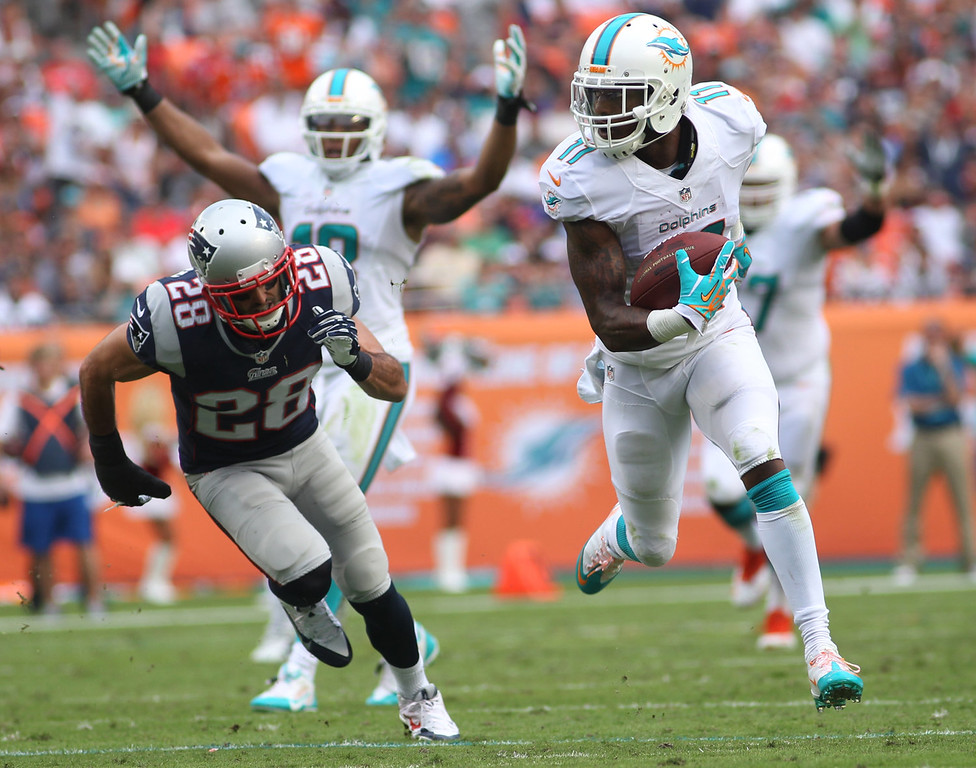 . Miami Dolphins wide receiver Mike Wallace (11) runs for a touchdown as New England Patriots strong safety Steve Gregory (28) can\'t keep up during the first half of an NFL football game, Sunday, Dec. 15, 2013, in Miami Gardens, Fla. (AP Photo/J Pat Carter)