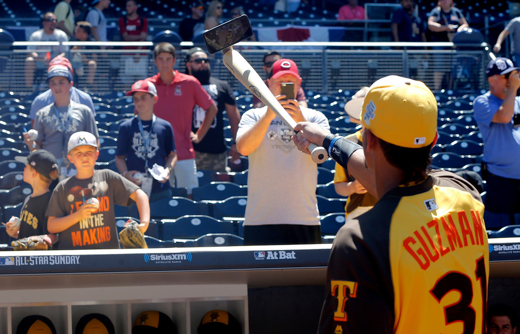 . World Team\'s Ronald Guzman (31), of the Texas Rangers, takes a selfie as fans take pictures prior to the All-Star Futures baseball game against the U.S. team, Sunday, July 10, 2016, in San Diego. (AP Photo/Lenny Ignelzi)