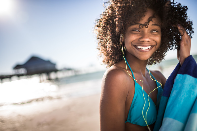 Portrait of a young African American girl smiling on the beach.