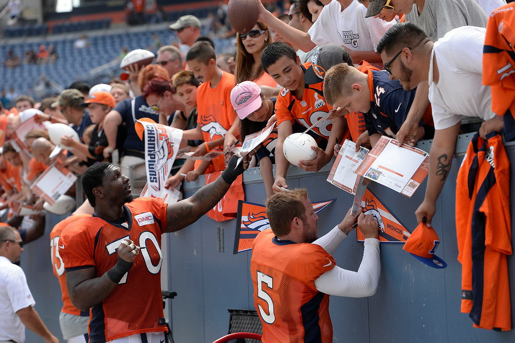 . Denver Broncos offensive tackle Vinston Painter (70) and Denver Broncos kicker Matt Prater (5) sign autographs after practice on day four of the Denver Broncos 2014 training camp July 27, 2014 at Sports Authority Field at Mile High. (Photo by John Leyba/The Denver Post)