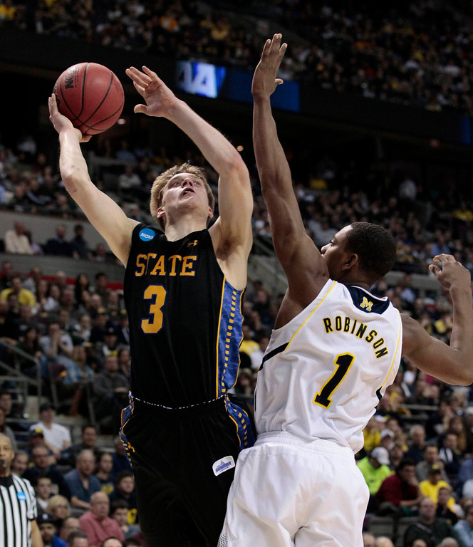 . South Dakota State Jackrabbits\' Nate Wolters (L) shoots as Michigan Wolverines\' Glenn Robinson III defends during the second half of their second round NCAA tournament basketball game in Auburn Hills, Michigan March 21, 2013.  REUTERS/ Jeff Kowalsky