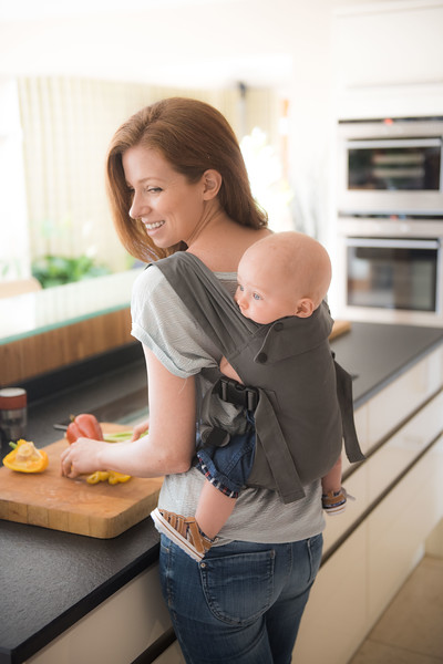 Izmi_Baby_Carrier_Mid_Grey_Lifestyle_Back_Carry_Mum_Smiling_At_Baby_Kitchen_View.jpg