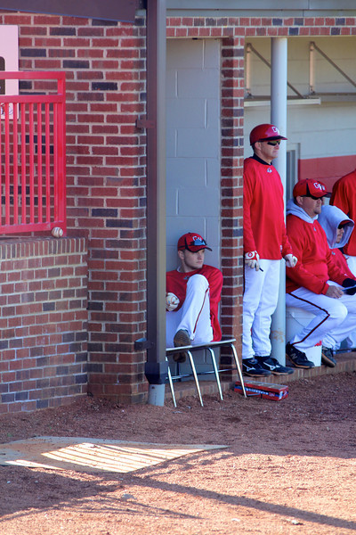 GW players and coaches watch from the dugout