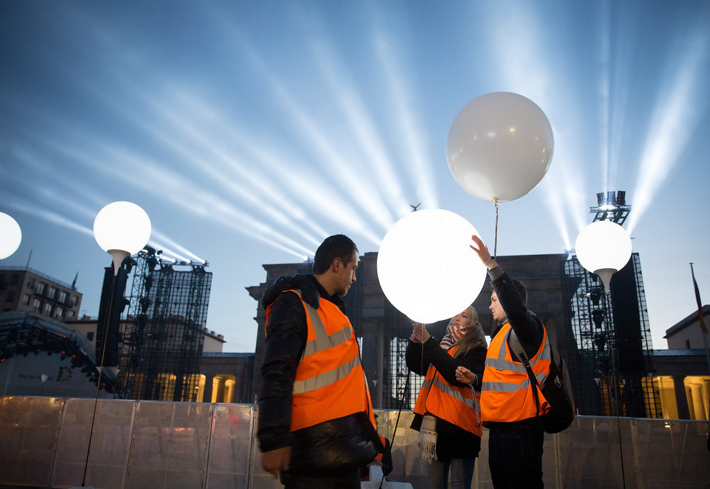 ". Balloons of the art installation \'Lichtgrenze 2014\' (""light border 2014\'\"") are swapped against balloons filled with helium in front of Brandenburg Gate in Berlin Sunday, Nov. 9, 2014. The helium filled balloons will be set free along the line of the former Berlin Wall on Sunday evening, the 25th anniversary of the opening of the iron curtain in the divided city. (AP Photo/dpa, Kay Nietfeld)"