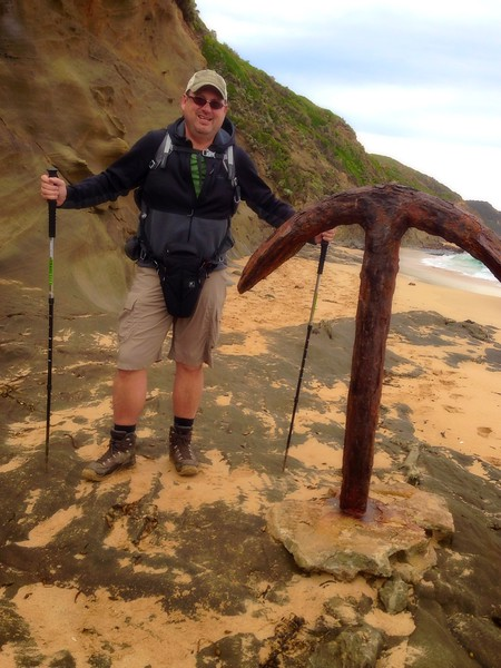 A boomer hiker stands on the beach beside an anchor buried in the sand in Australia.