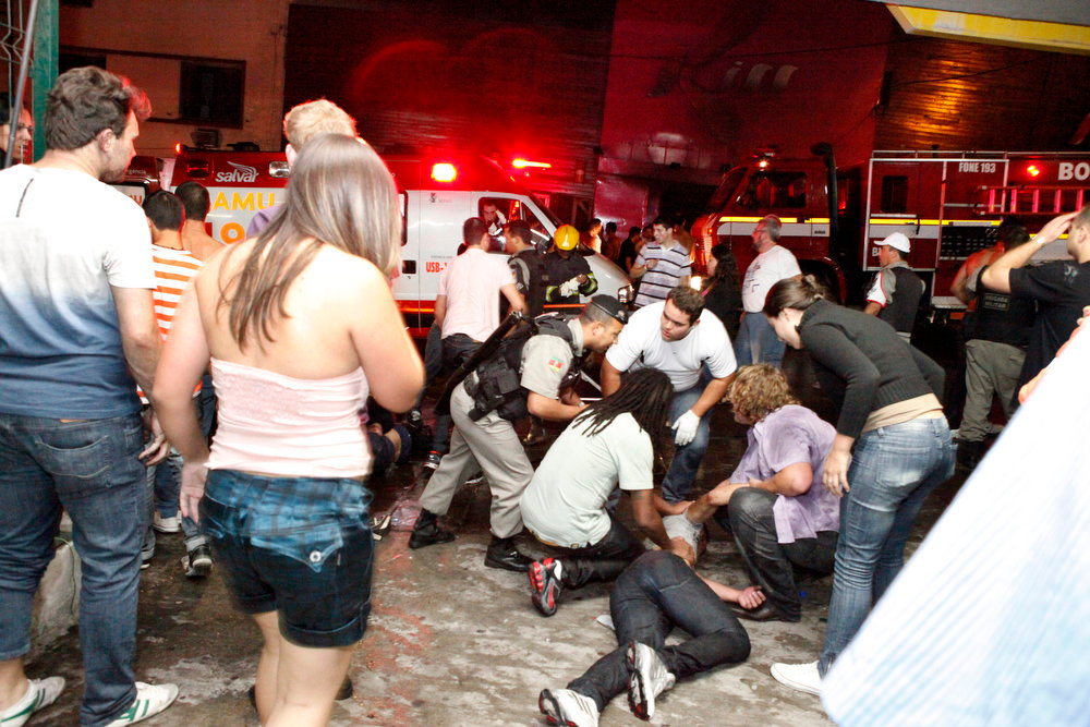 . People help an injured man, victim of a fire in a club in Santa Maria city, Rio Grande do Sul state,  Brazil,  Sunday, Jan. 27,  2013.  According to police more than 200 died in the devastating nightclub fire in southern Brazil.  Officials say the fire broke out at the Kiss club in the city of Santa Maria while a band was performing. At least 200 people were also injured. (AP Photo/Agencia RBS)