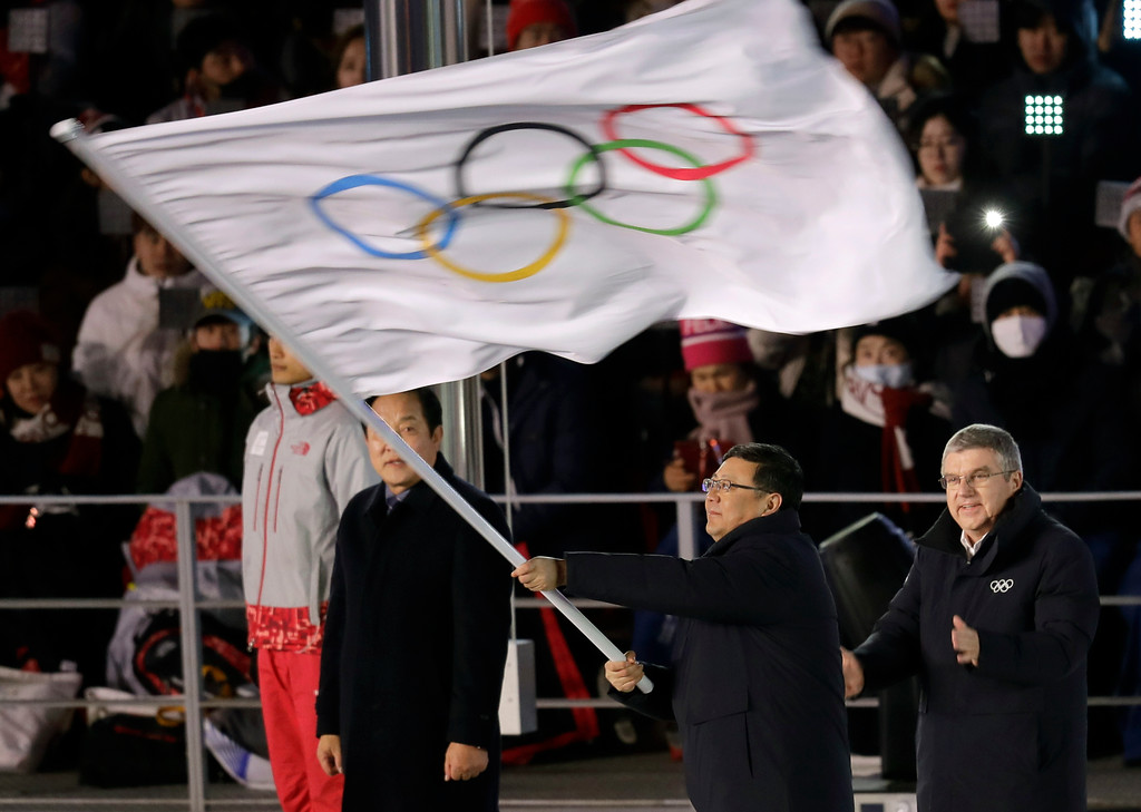 . Chen Jining, mayor of Beijing waves the Olympic flag as Thomas Bach, president of the International Olympic Committee watches during the closing ceremony of the 2018 Winter Olympics in Pyeongchang, South Korea, Sunday, Feb. 25, 2018. (AP Photo/Michael Probst)