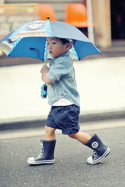 Boy walking in the rain in Tokyo. Hirajuku