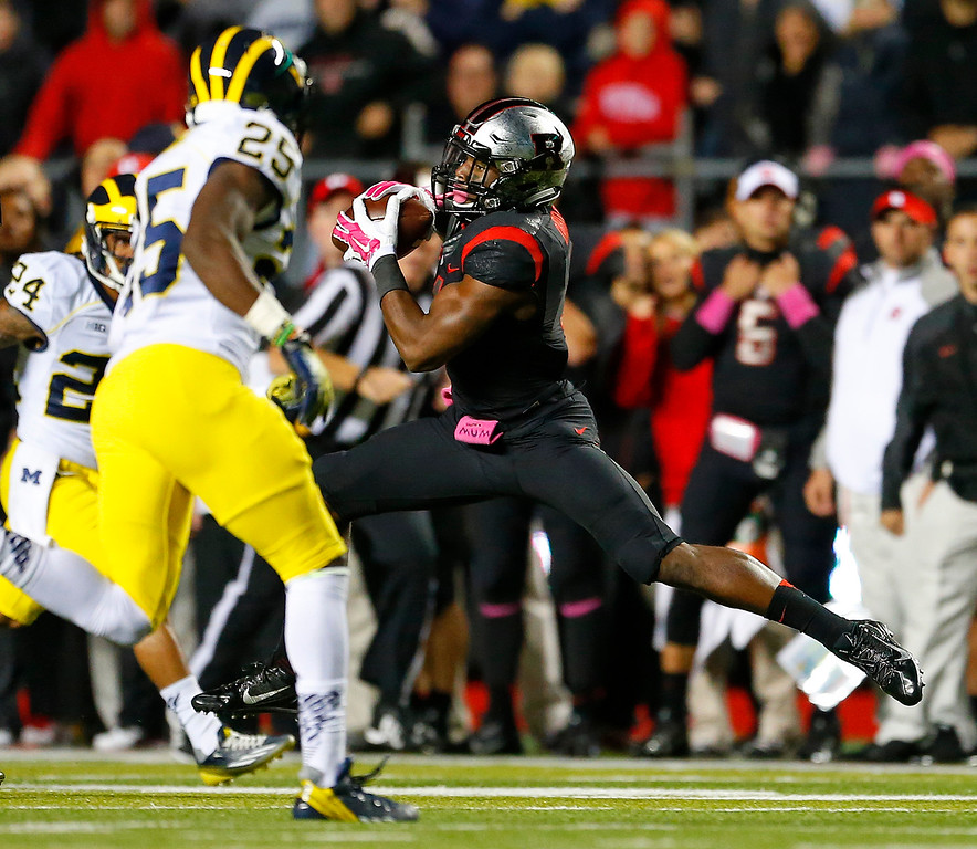. Rutgers wide receiver Leonte Carroo (4) makes a catch for a first down between Michigan defenders Delonte Hollowell (24) and Dymonte Thomas (25) during the second half of an NCAA college football game Saturday, Oct. 4, 2014, in Piscataway, N.J. Rutgers defeated Michigan 26-24. (AP Photo/Rich Schultz)